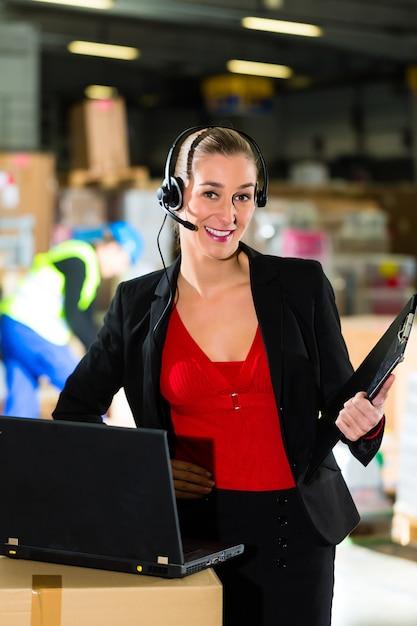 Friendly woman, dyspozytor lub przełożony korzystający z zestawu słuchawkowego i laptopa w magazynie firmy spedycyjnej, Premium Zdjęcia