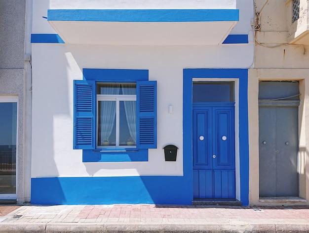 Frontowa Fasada Budynek Mieszkalny Z Błękitnymi Drzwiami I Okno Premium Zdjęcia