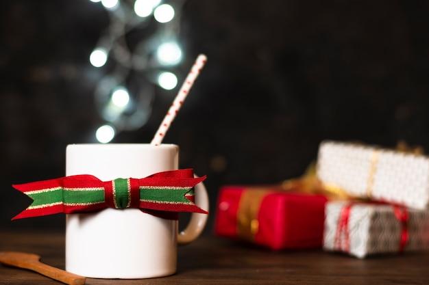 Frontowego widoku biała filiżanka herbata z bożonarodzeniowe światła w tle Darmowe Zdjęcia