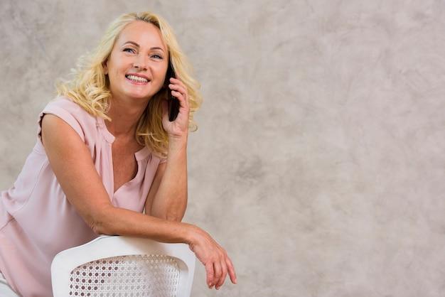 Frontowego widoku blondynki dama opowiada na telefonie z kopii przestrzenią Darmowe Zdjęcia