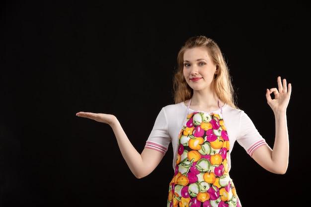 Frontowego Widoku Młoda Atrakcyjna Dziewczyna W Kolorowym Przylądku Pokazuje Ręka Znaki Ono Uśmiecha Się Na Czarnym Tle Czyści Gospodyni Domowej Darmowe Zdjęcia