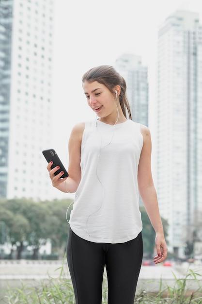 Frontowego widoku młoda kobieta sprawdza jej telefon Darmowe Zdjęcia