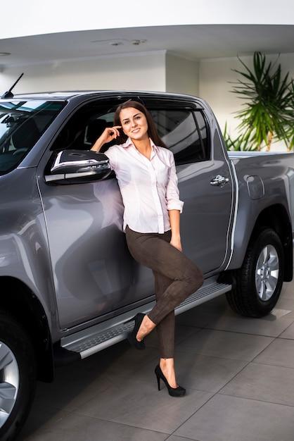 Frontowego Widoku Smiley Kobieta Pozuje Obok Samochodu Darmowe Zdjęcia