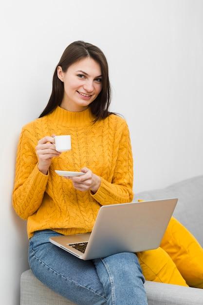 Frontowy Widok Kobieta Trzyma Filiżankę Kawy Z Laptopem Na Podołku Darmowe Zdjęcia