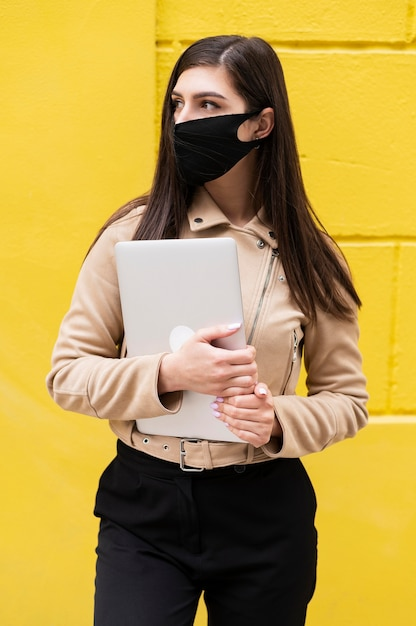 Frontowy Widok Kobieta Z Twarzy Maski Mienia Laptopem Premium Zdjęcia