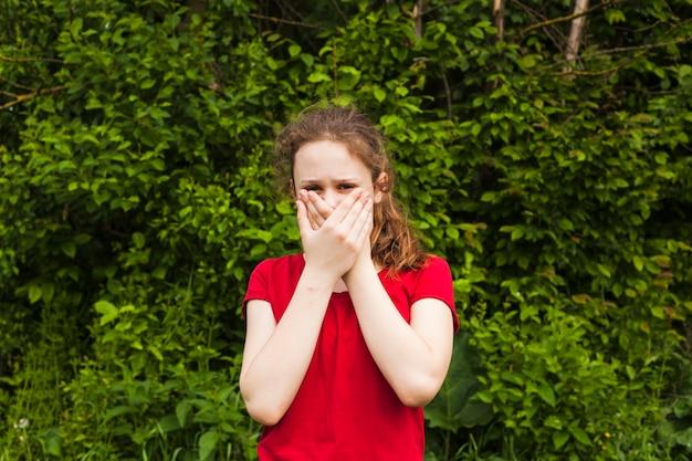 Frontowy Widok Patrzeje Kamerę Zakrywa Jej Usta Przy Parkiem Dziewczyna Darmowe Zdjęcia