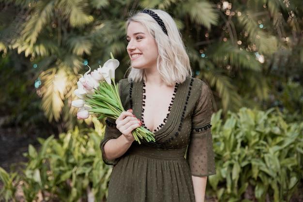 Frontowy Widok Pozuje Szczęśliwa Kobieta Podczas Gdy Trzymający Tulipany Darmowe Zdjęcia