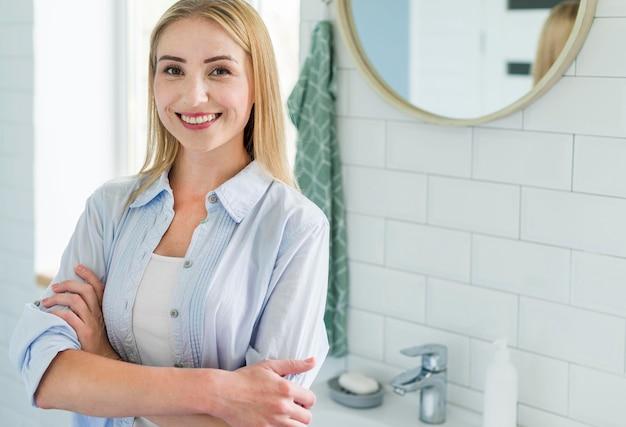 Frontowy Widok Pozuje W łazience Z Kosmetykami Kobieta Darmowe Zdjęcia