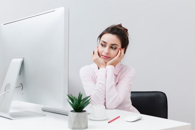 Frontowy Widok Pracuje Przy Biurkiem I Patrzeje Komputer Urocza Kobieta Darmowe Zdjęcia