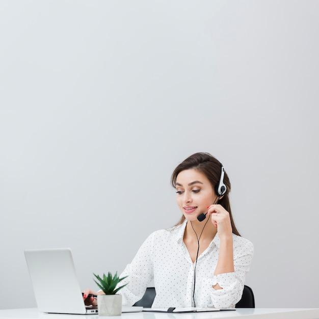 Frontowy Widok Pracuje Przy Biurkiem Kobieta Podczas Gdy Będący Ubranym Słuchawki I Patrzejący Laptop Darmowe Zdjęcia