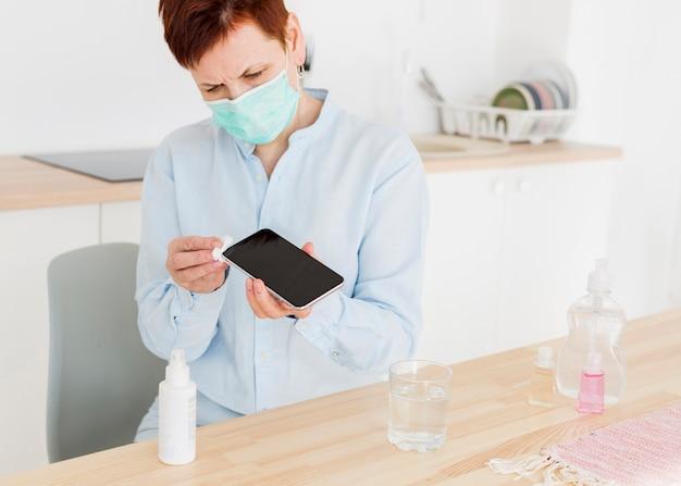 Frontowy Widok Starsza Kobieta Dezynfekuje Jej Smartphone W Domu Z Medyczną Maską Darmowe Zdjęcia