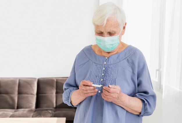 Frontowy Widok Starsza Kobieta Patrzeje Termometr Z Medyczną Maską Darmowe Zdjęcia