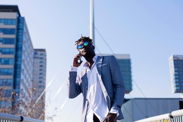 Frontowy widok uśmiechnięty młody czarnego afrykanina mężczyzna jest ubranym eleganckie ubrania stoi w ulicie podczas gdy używać telefon komórkowego outdoors w słonecznym dniu Premium Zdjęcia