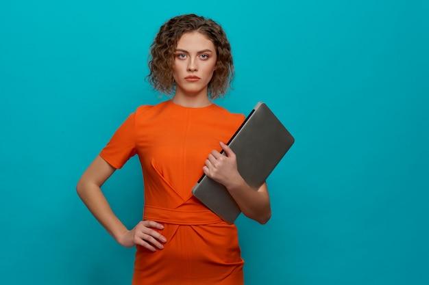 Frontowy widok utrzymuje komputer w rękach poważna kobieta Premium Zdjęcia