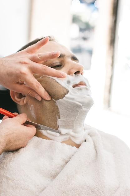 Fryzjer Goli Brodę Człowiekowi Z Brzytwą W Zakładzie Fryzjerskim Premium Zdjęcia