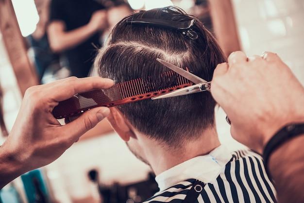 Fryzjer oślepia wzór na głowie klienta. Premium Zdjęcia