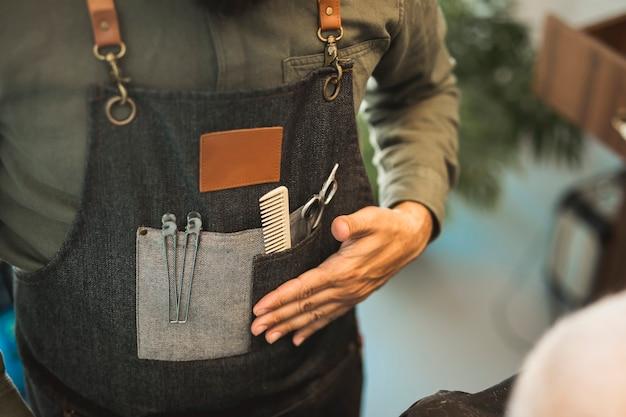 Fryzjer w fartuchu z narzędziami do strzyżenia Darmowe Zdjęcia