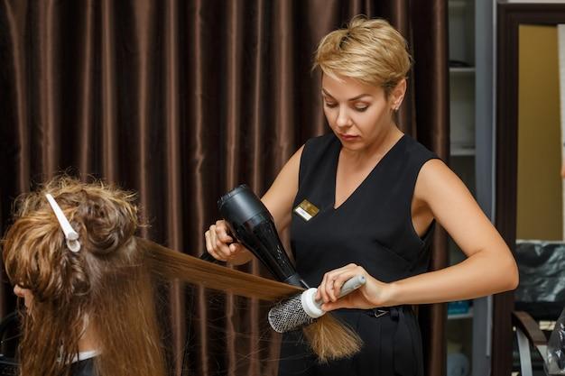 Fryzjer wysusza włosy klientowi za pomocą suszarki do włosów. Premium Zdjęcia