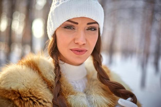 Futrzana kamizelka na pięknej młodej kobiecie rasy białej w zimowym słonecznym lesie Premium Zdjęcia