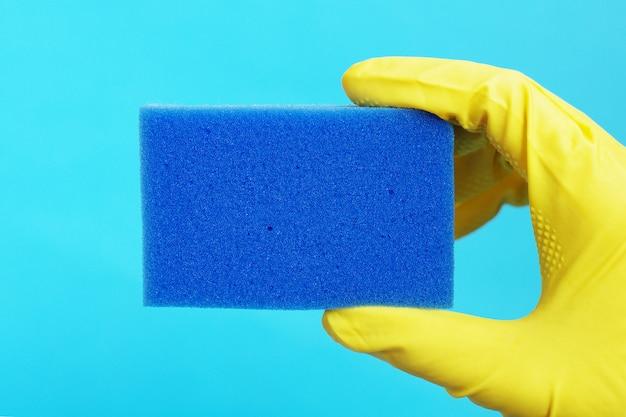 Gąbka do mycia naczyń w dłoni w żółtej gumowej rękawicy Premium Zdjęcia