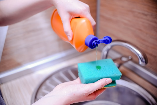Gąbka do naczyń z mydłem do mycia naczyń. koncepcja czyszczenia domu. Premium Zdjęcia