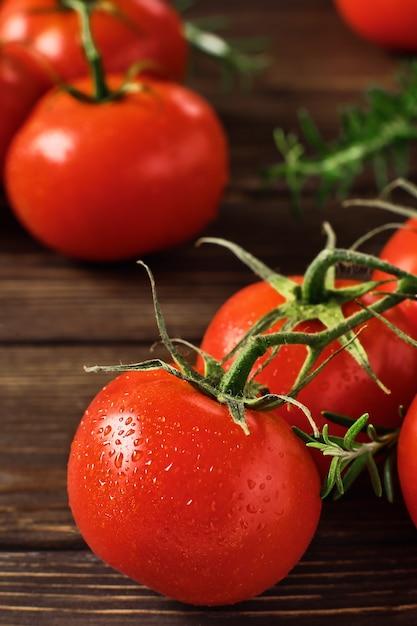 Gałęzie Dojrzałych Czerwonych Pomidorów I Gałązek Rozmarynu Na Ciemnym Drewnianym Stole Premium Zdjęcia