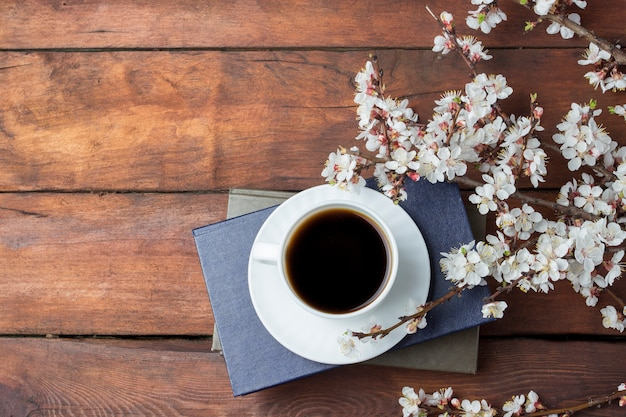 Gałęzie Sakura Z Kwiatami, Biały Kubek Z Czarną Kawą I Książka Na Ciemnej Drewnianej Powierzchni. Leżał Płasko, Widok Z Góry Premium Zdjęcia