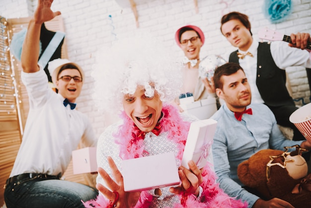 Gay faceci w muszce otwierają prezenty na imprezie. Premium Zdjęcia