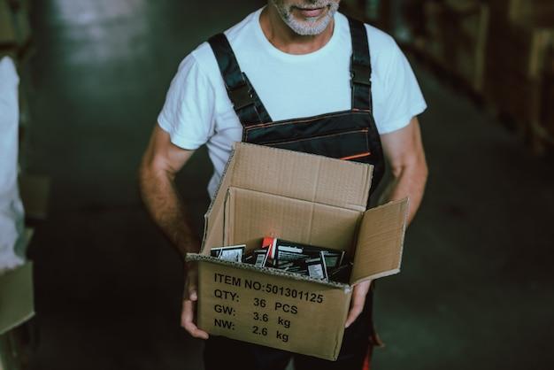 Ged mężczyzna ma na sobie mundur trzymając karton Premium Zdjęcia