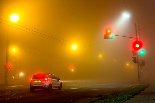 Gęsta Mgła Nad Pustą Drogą Z Samotnym Samochodem I światłami W Nocy Premium Zdjęcia