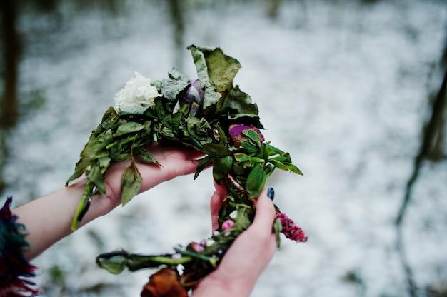 Ggirl gospodarstwa wieniec na ręce w śnieżnym lesie w zimowy dzień. Premium Zdjęcia