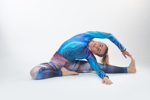Gimnastyczka W Wielokolorowych Rajstopach Podczas Rozciągania Darmowe Zdjęcia