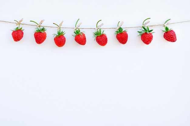 Girlanda czerwone dojrzałe truskawki wiesza na drewnianym clothespin na linowym dratwie na białym drewnianym tle Premium Zdjęcia
