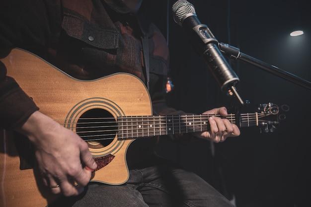 Gitarzysta Gra Na Gitarze Akustycznej Z Kapodasterem Przed Mikrofonem Darmowe Zdjęcia