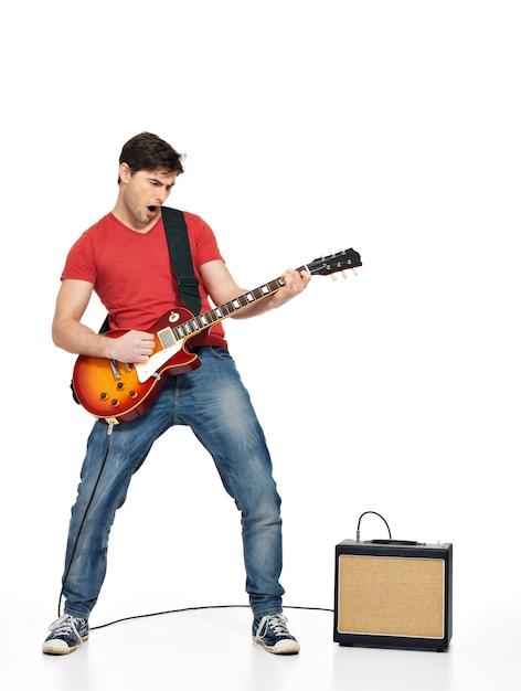 Gitarzysta Mężczyzna Gra Na Gitarze Elektrycznej Z Jasnymi Emocjami, Na Białym Tle Na Białej ścianie Darmowe Zdjęcia