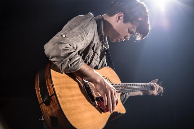 Gitarzysta, Muzyka. Młody Mężczyzna Gra Na Gitarze Akustycznej Na Czarnym Tle Odizolowane. Spiczaste światło Darmowe Zdjęcia
