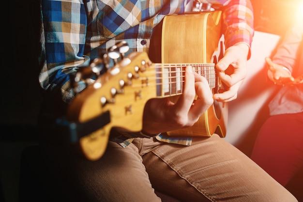 Gitarzysta trzyma gitarę z bliska Premium Zdjęcia