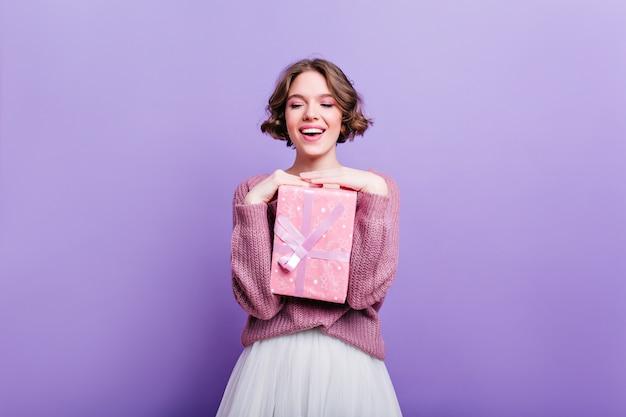 Glamorous Dziewczyna Z Kręconymi, Krótkimi Włosami, Pozująca Z Różowym Pudełkiem I śmiejąc Się. Atrakcyjna Modelka Z Prezentem Na Boże Narodzenie Na Białym Tle Na Fioletowej ścianie I Uśmiechnięty. Darmowe Zdjęcia