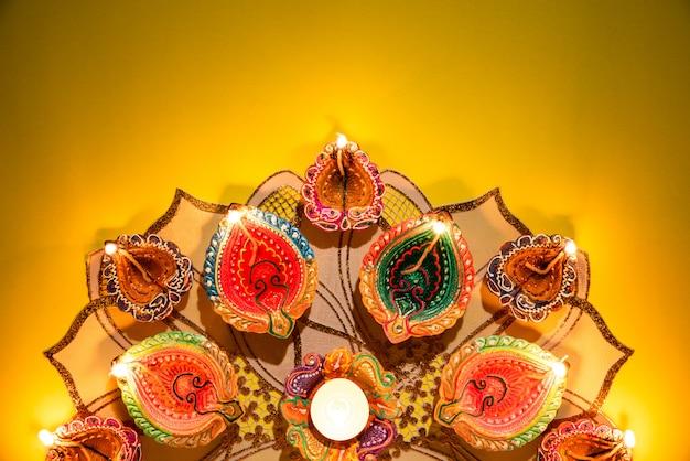 Gliniane diya lampy zaświecające podczas dipavali świętują na żółtym tle Premium Zdjęcia