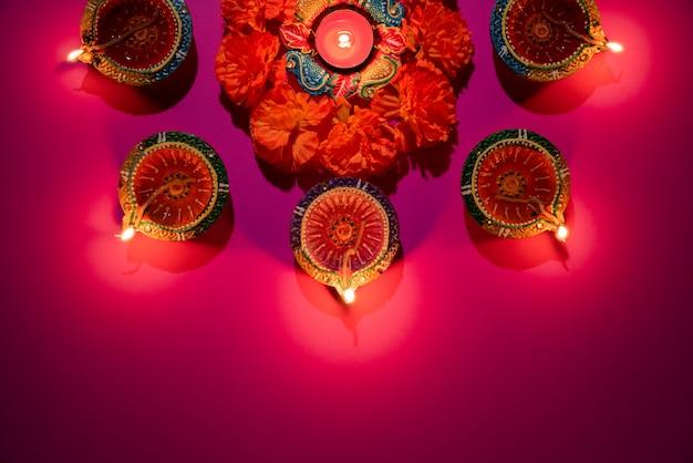 Gliniane lampy diya zapalone podczas dipavali świętują na różowym tle Premium Zdjęcia