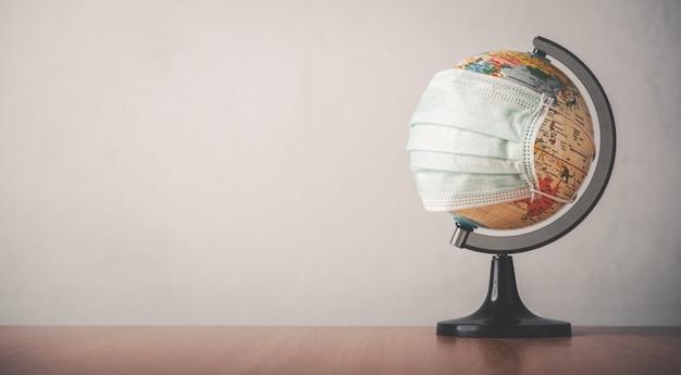 Globus Pokryty Jest Maską Na Drewnianej Podłodze. Koncepcja Polega Na Nałożeniu Maski, Aby Zatrzymać Wirusa Covid-19. Premium Zdjęcia