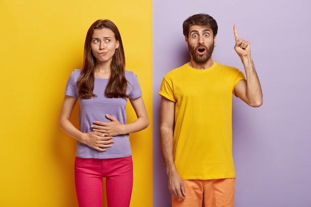 Głodna Ciemnowłosa Kobieta Dotyka Brzucha, Chce Zjeść Coś Smacznego, Nosi Fioletową Koszulkę I Różowe Spodnie Darmowe Zdjęcia