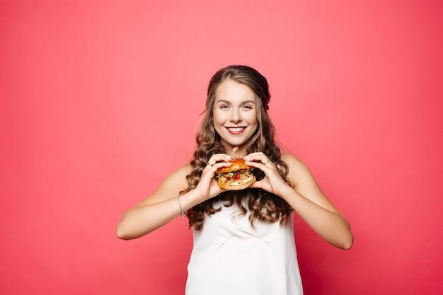 Głodna dziewczyna z otwartym usta je dużego hamburger. Premium Zdjęcia