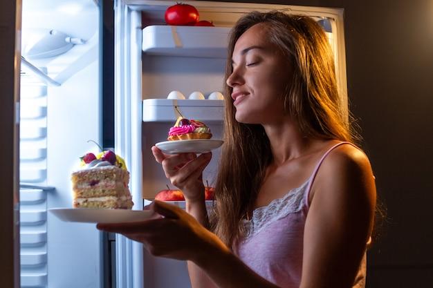 Głodna Kobieta W Piżamie Je Produkty Z Mąki Nocą W Pobliżu Lodówki. Przestań Dietę I Zdobądź Dodatkowe Kilogramy Z Powodu Węglowodanów I Niezdrowego Jedzenia Premium Zdjęcia