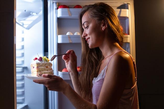 Głodna Kobieta W Piżamie Jedząca Słodkie Ciasto Nocą W Pobliżu Lodówki. Przestań Dietę I Zyskaj Dodatkowe Kilogramy Z Powodu śmieciowych Węglowodanów I Niezdrowego Nocnego Jedzenia Premium Zdjęcia