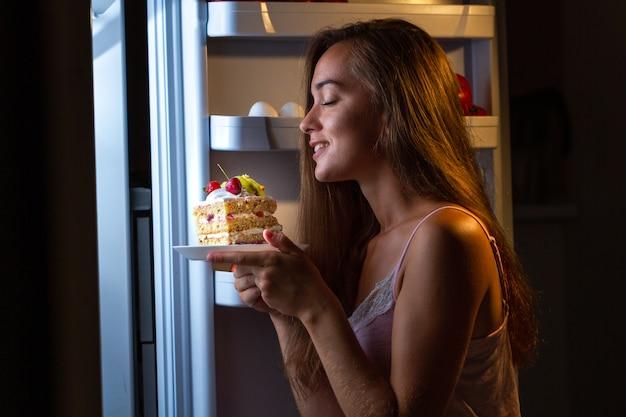 Głodna Kobieta W Piżamie Jedząca Słodkie Ciasto Nocą W Pobliżu Lodówki Premium Zdjęcia