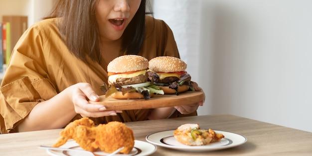Głodna Z Nadwagą Kobieta Trzyma Hamburger Na Drewnianym Talerzu, Pieczonym Kurczaku I Pizzy Na Stole Premium Zdjęcia