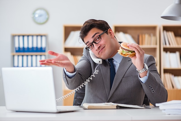 Głodny zabawny biznesmen jedzenie fast foodów kanapkę Premium Zdjęcia