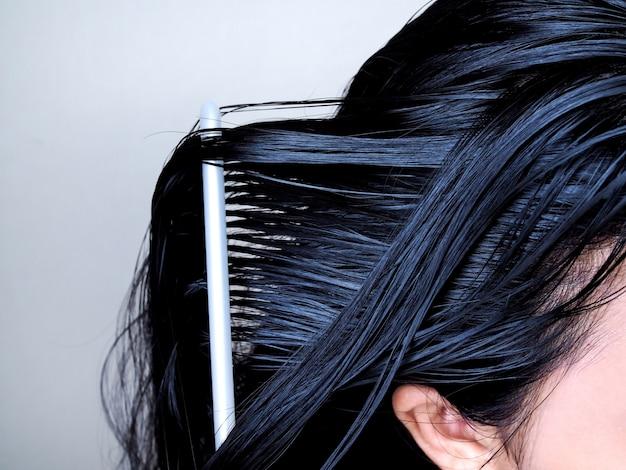 Głowa azjatki o długich czarnych włosach, czesanie włosów szczotką do włosów. zdrowie linii włosów. Premium Zdjęcia