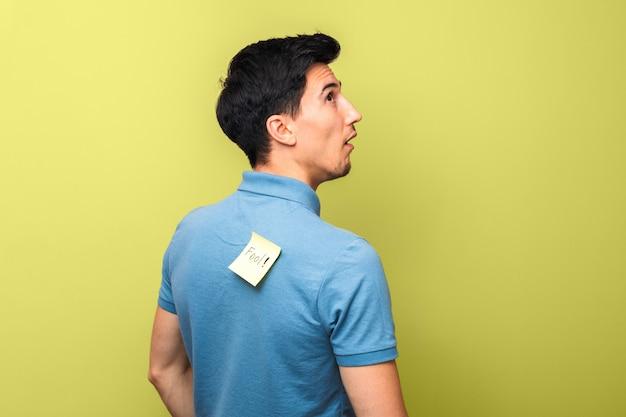 Głupi Mężczyzna W Niebieskiej Koszulce Polo Z żółtą Karteczką Z Głupcem Na Plecach Głupio Patrząc W Górę Premium Zdjęcia
